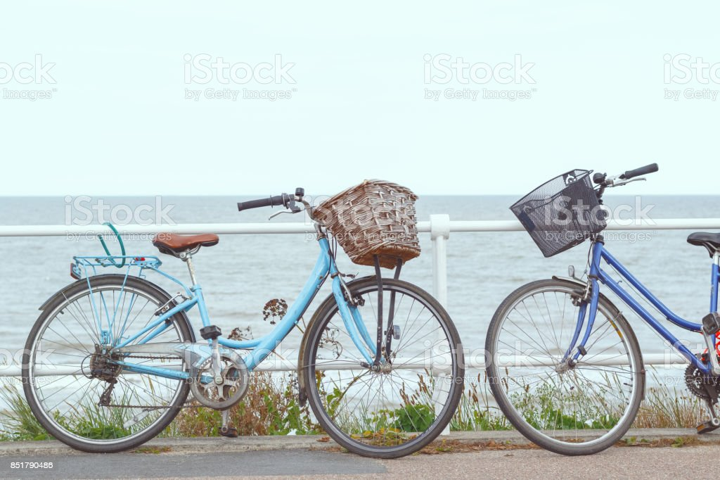 Two bicycles chained to the fence of promenade in Southwold, UK stock photo