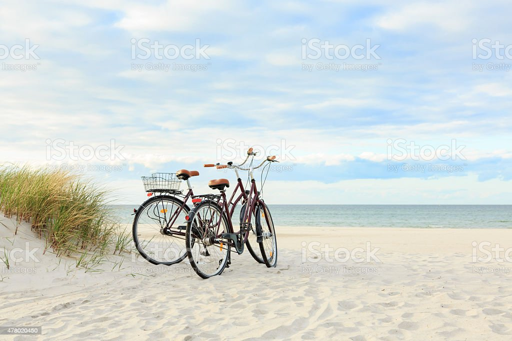 Two bicycles on beach stock photo