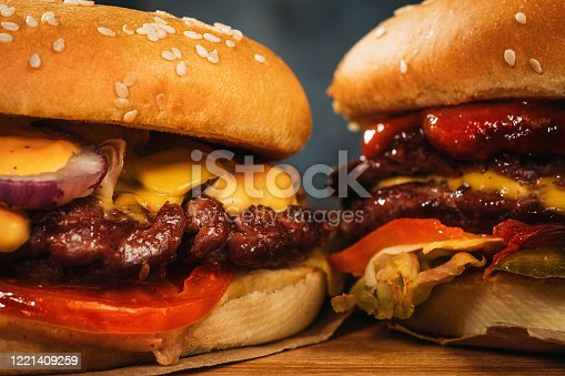 Two big homemade burgers or hamburgers with big roasted meat, close up.