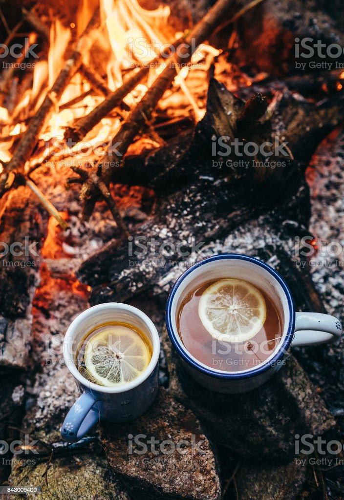 Two big mugs of tea with lemon near campfire stock photo