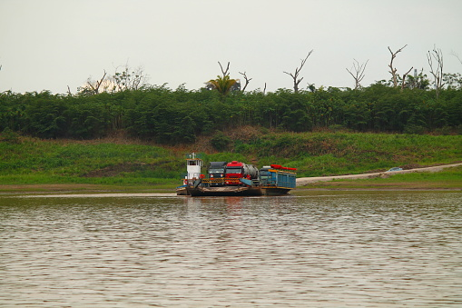 1131408581 istock photo two big trucks on a ferry in the brazilian jungle 660441820