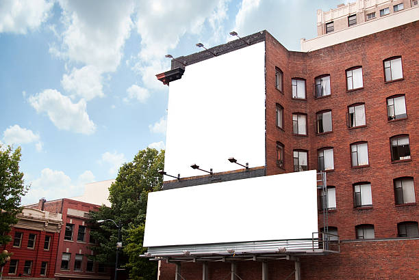 two billboards on brick building - symmetry stock photos and pictures