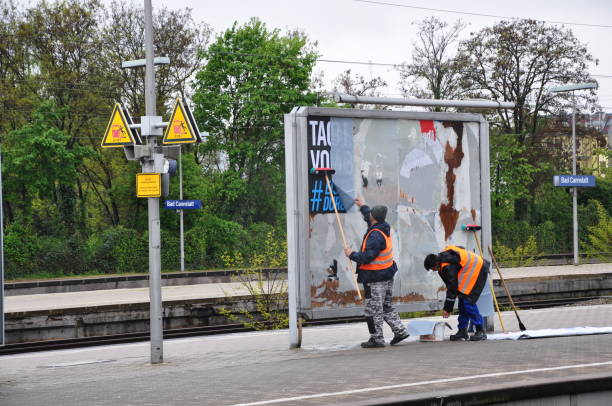 Two billposters stick an advertising poster at the railway station. - foto stock