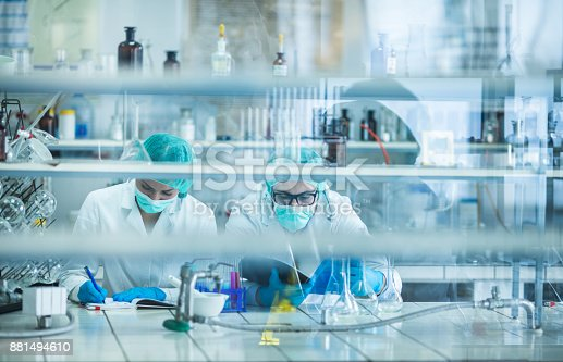 499203366 istock photo Two biotechnologists examining data for medical research in the laboratory. 881494610