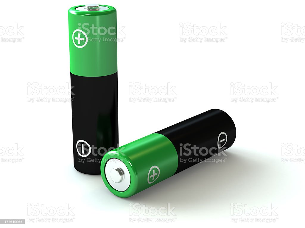 Two black and green AA batteries stock photo