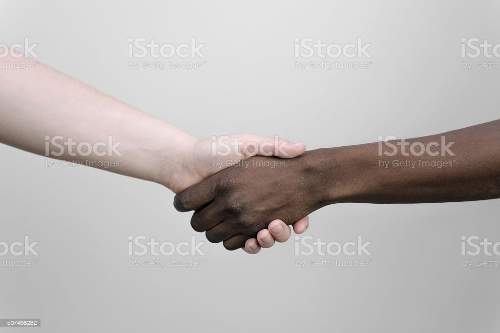 two black and white hands joining together for diversity. stock photo
