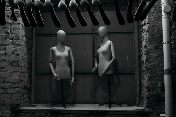 zwei schwarz-weiße Schaufensterpuppen in der Ecke des Ladens während des Verkaufs – Foto