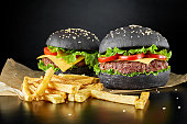 istock Two black burgers with french fries 684063834