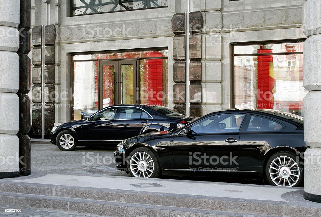 Two black cars in front of a building stock photo