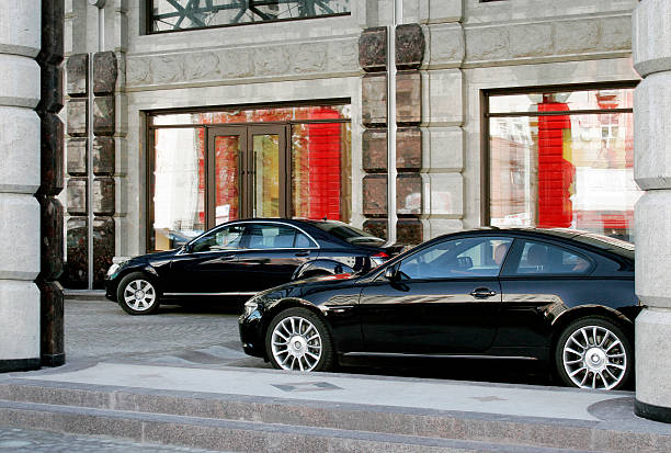two black cars in front of a building - limousine service stock photos and pictures