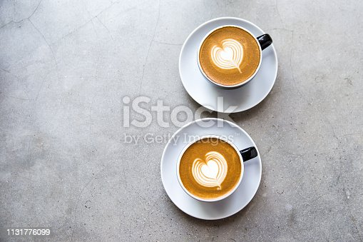 istock Two black cups of tasty cappucino with love art latte. 1131776099