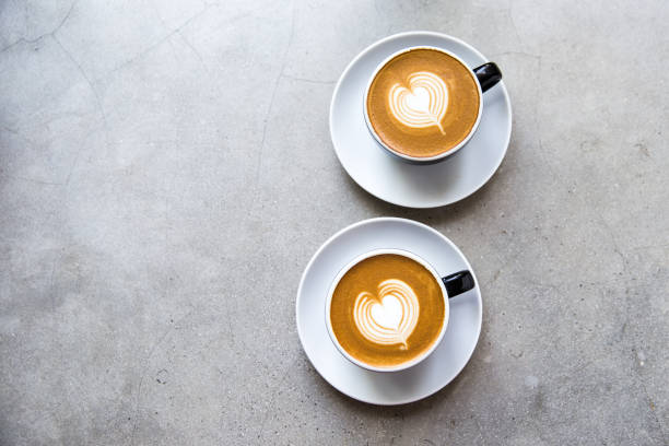 dois copos pretos do cappucino saboroso com latte da arte do amor. - dois objetos - fotografias e filmes do acervo