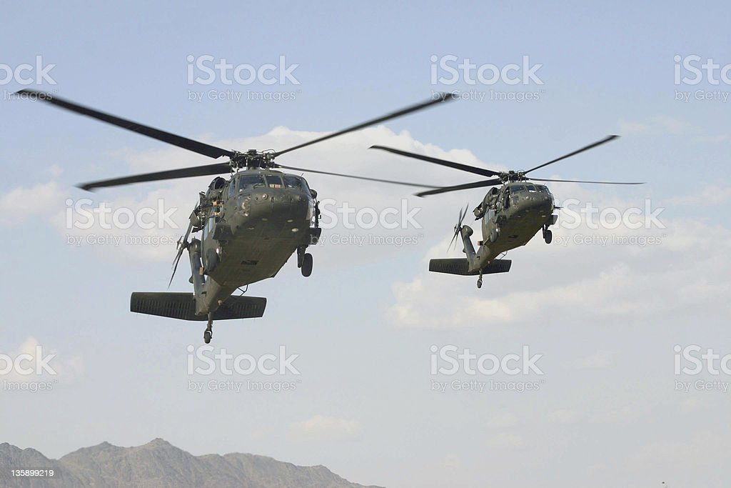 Two black hawk helicopters flying in the sky stock photo