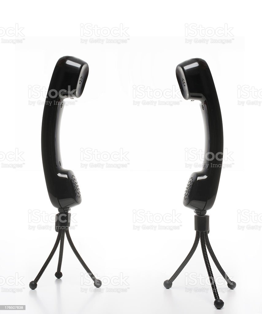 two black phone receivers on mini tripods royalty-free stock photo