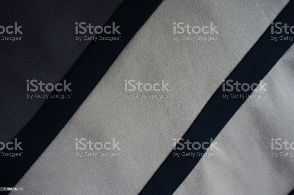 Two black ribbons sewn to grey and beige fabric stock photo