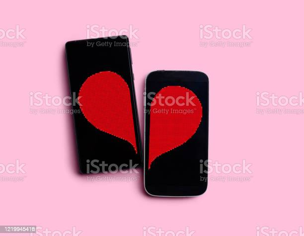 Two Black Smartphones On A Pink Background With A Heart Figure The Concept Of Love Dating Meeting Websiteat A Distance On The Internet And Social Networks Without People Stock Photo - Download Image Now
