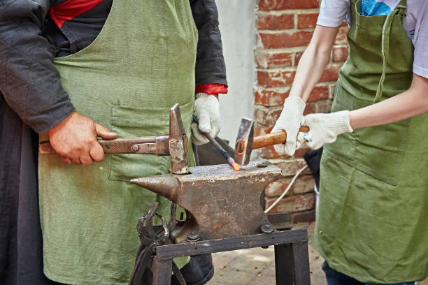 Two blacksmiths, an experienced one and his apprentice Two blacksmiths, an experienced one and his apprentice, work on an anvil with hammers in their hands. anvil stock pictures, royalty-free photos & images