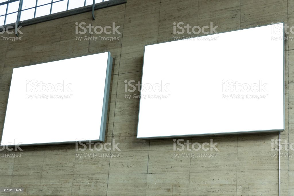 Two blank ad space signs on stone wall from the side