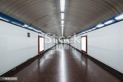 Two blank billboards inside a subway station corridor