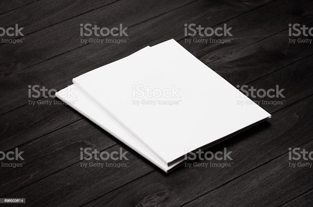 Two blank corporate identity broshure on black stylish wood background, mock up. stock photo