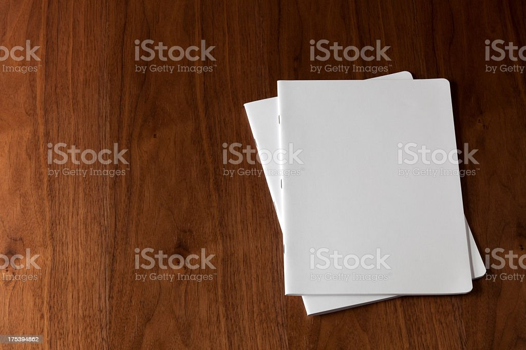 Two blank magazines on a wooden floor stock photo