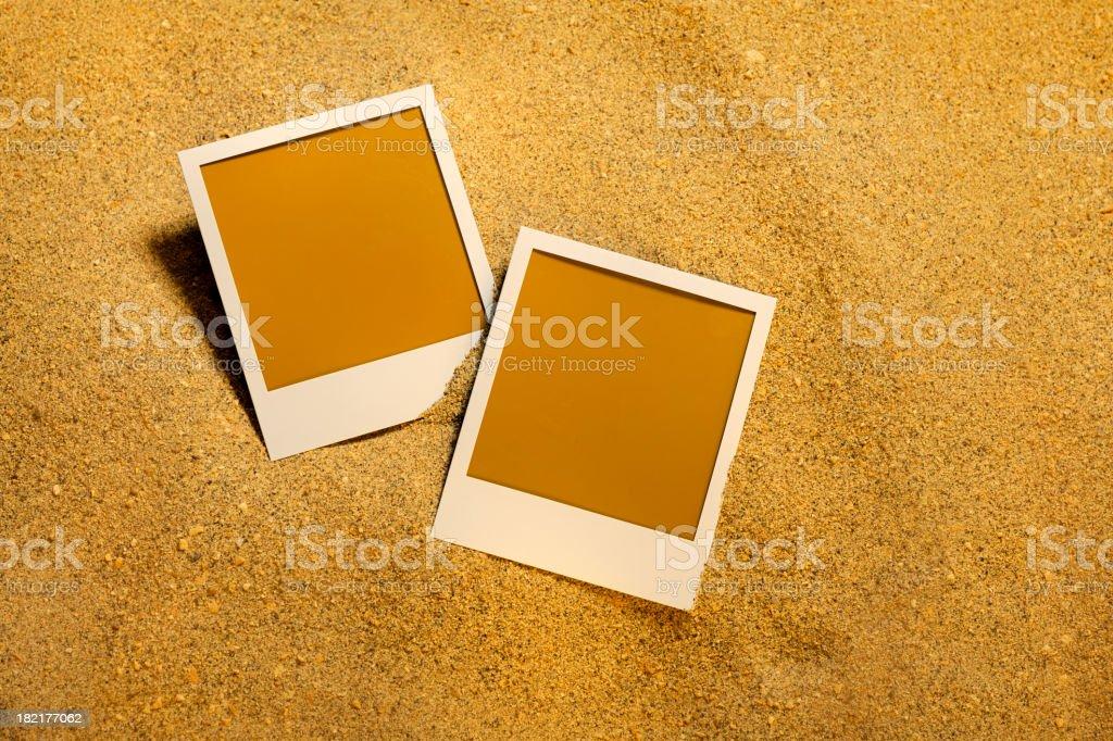 Two blank photos on a sandy beach background stock photo