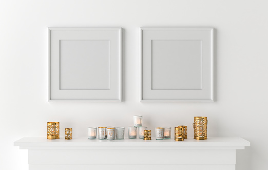Two blank picture frame with candles on fireplace