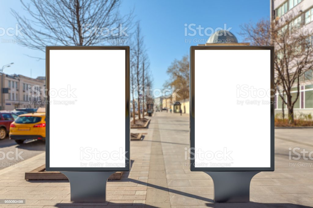 Two blank street billboard posters stand on city background.