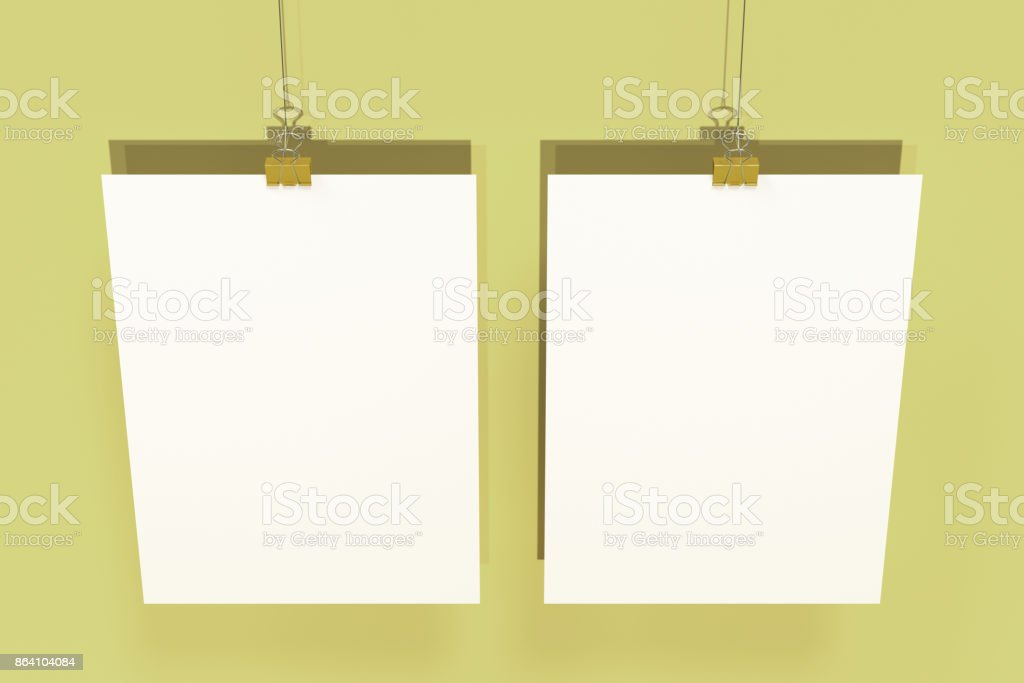 Two blank white posters with binder clip mockup on yellow background royalty-free stock photo