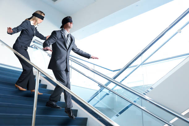 Two Blindfolded Business People Navigate Staircase stock photo