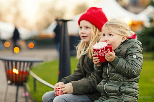 Two blonde child sisters drinking hot chocolate at winter european christmas market stock photo