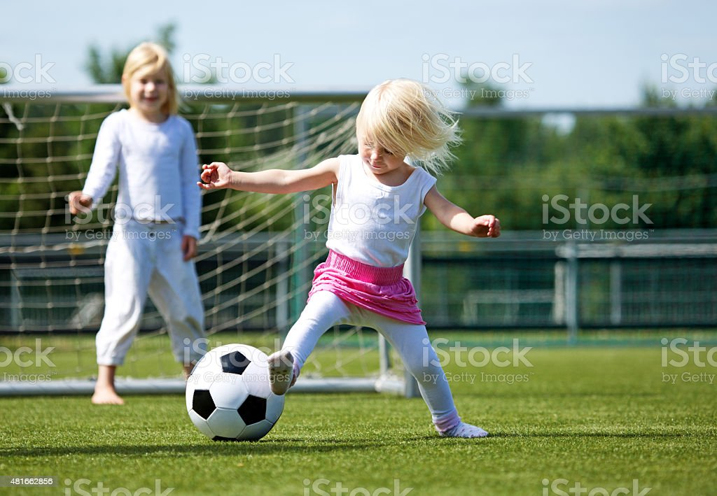 Two blonde sisters playing football stock photo