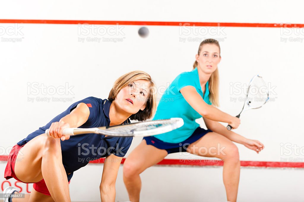 Two blonde women in action playing squash racket sport  stock photo