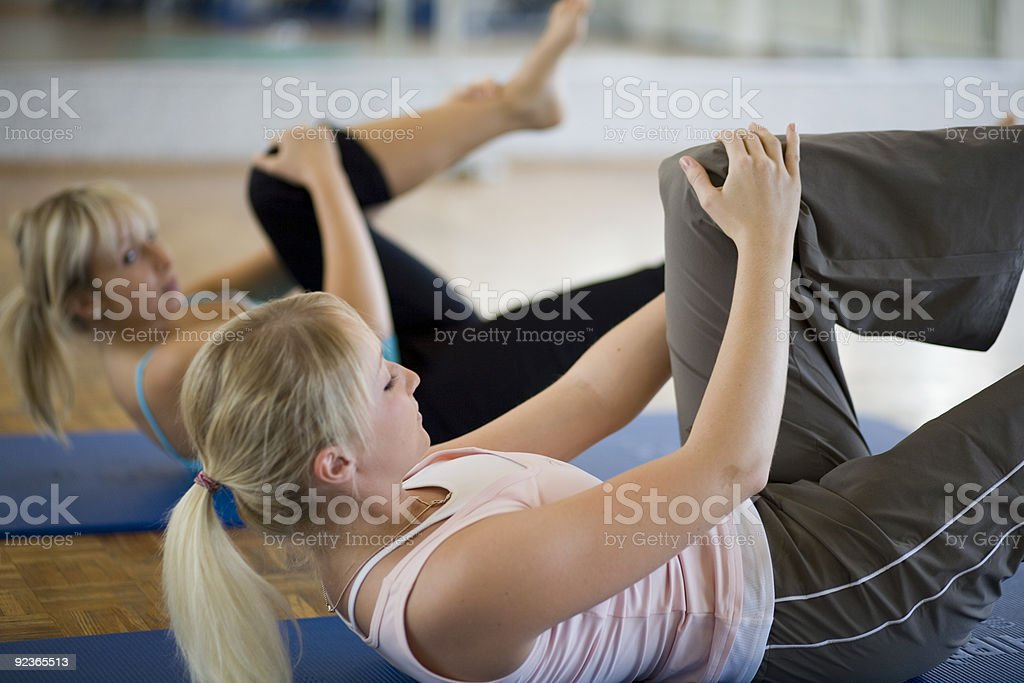 Two blonde women performing stretches on blue yoga mats royalty-free stock photo