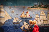 Istanbul, Turkey - July 10, 2019: Most of the new subway stations in Istanbul has big tile painting. Two woman walking in front of one of them. Ottoman sailboats are depicted in the pictures.