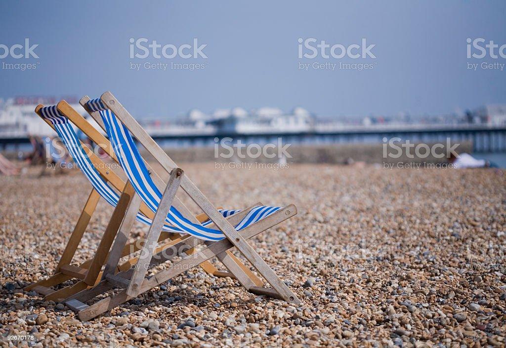 Two blue and white deckchairs on Brighton pebble beach, UK stock photo