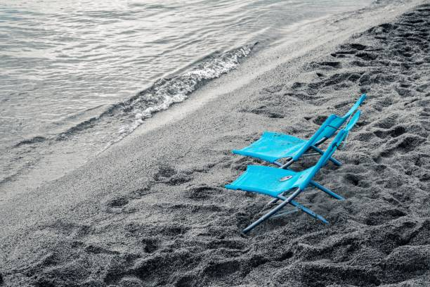 Two blue chairs on a sundy beach at sunset stock photo