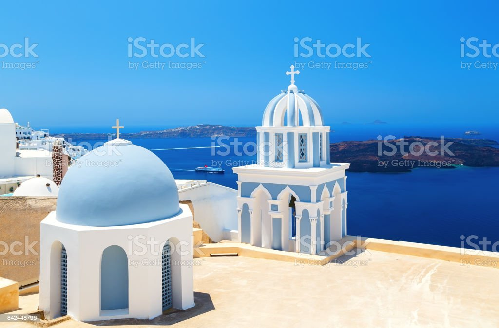 two blue domes of the beautiful Church of Fira, Santorini in background of Caldera and the sea stock photo