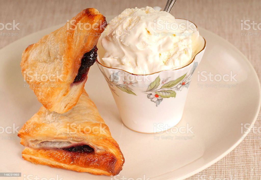Two blueberry turnovers with fresh whipped cream stock photo