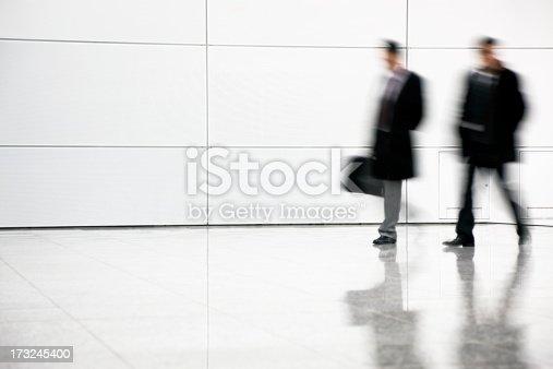 istock Two blurred businessmen walking in corridor 173245400