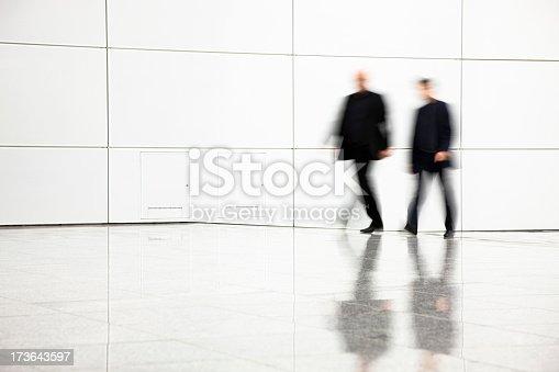 istock Two blurred businessmen walking in hallway 173643597