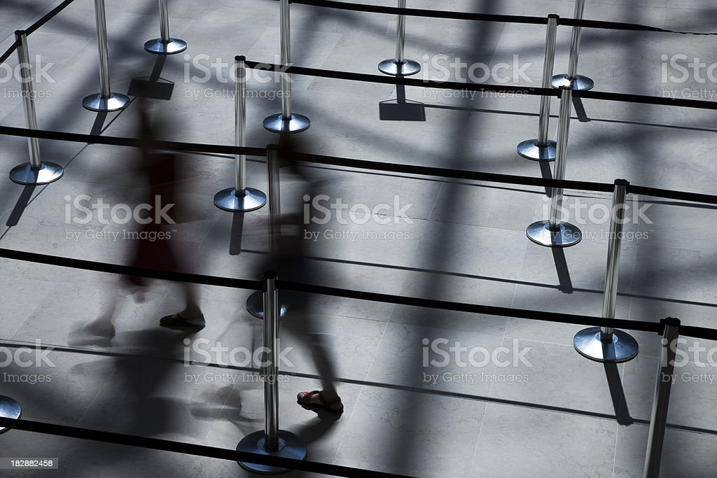 Two Blurred People Walking Through Empty Waiting Line stock photo