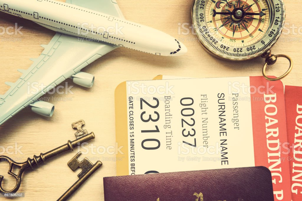 Two boarding passes with passports, vintage brass keys, a compass, a white model airplane on a table. stock photo