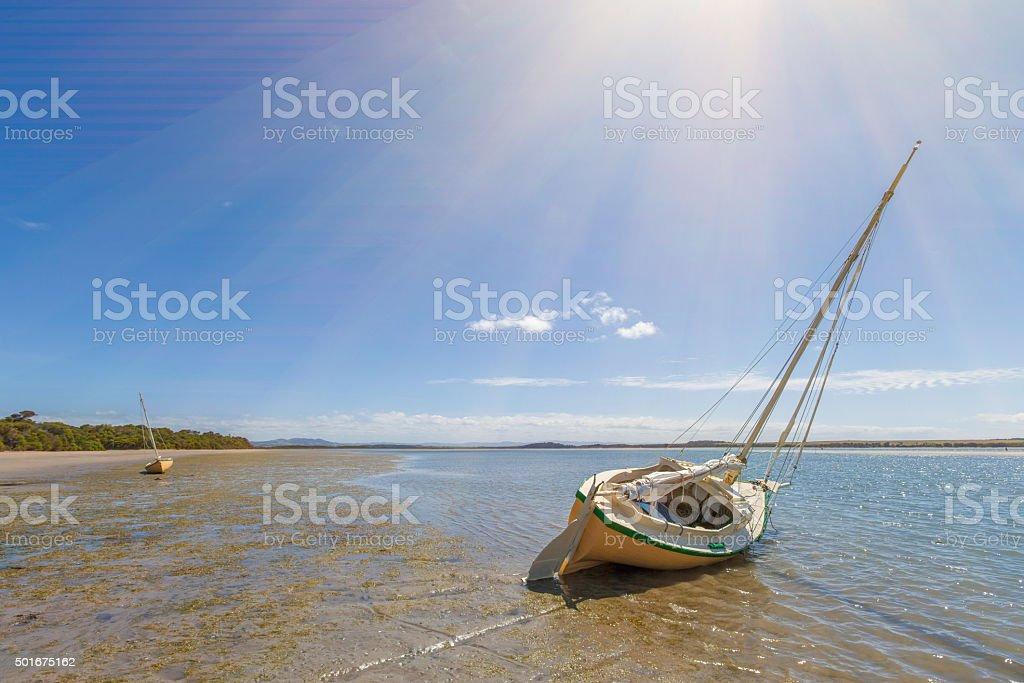 Two boats moored ona sand at Sandy Point beach, Australia stock photo