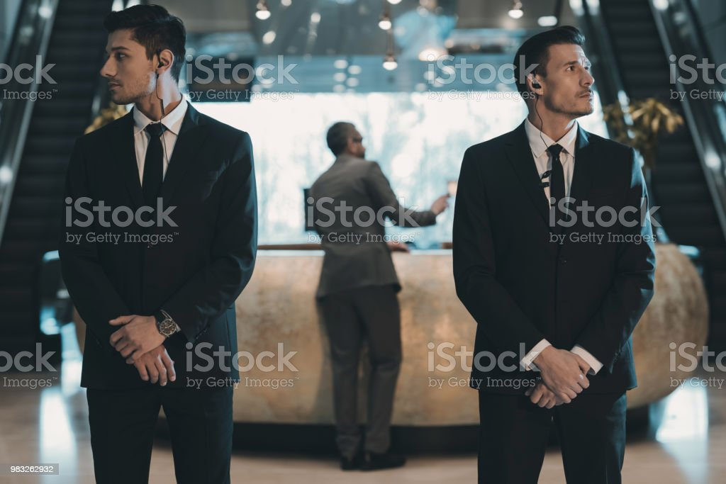 two bodyguards waiting for businessman standing at reception counter stock photo