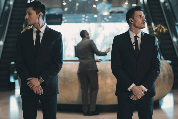 two bodyguards waiting for businessman standing at reception counter two bodyguards waiting for businessman standing at reception counter defend stock pictures, royalty-free photos & images