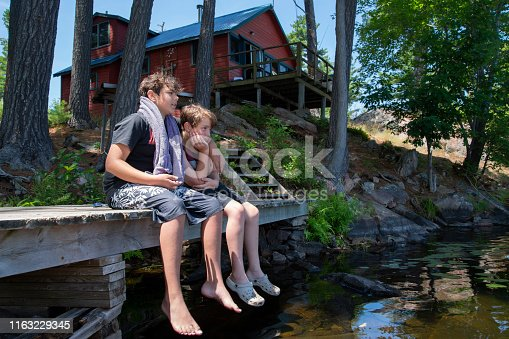 Two bothers relaxing on the dock of an island cabin or cottage.