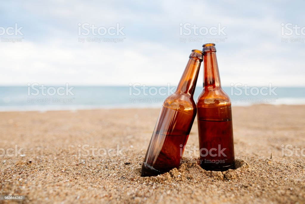 Two Bottles beer on sandy beach stock photo