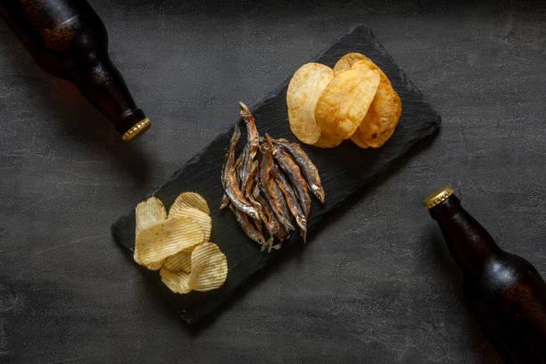 Duas garrafas de cerveja com batatas fritas e peixes secos de cheiro no fundo de pedra escura - foto de acervo