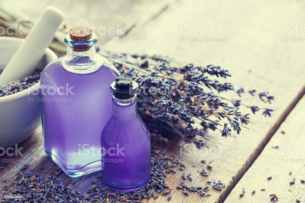 Two bottles of essential oil, mortar and lavender flowers. stock photo